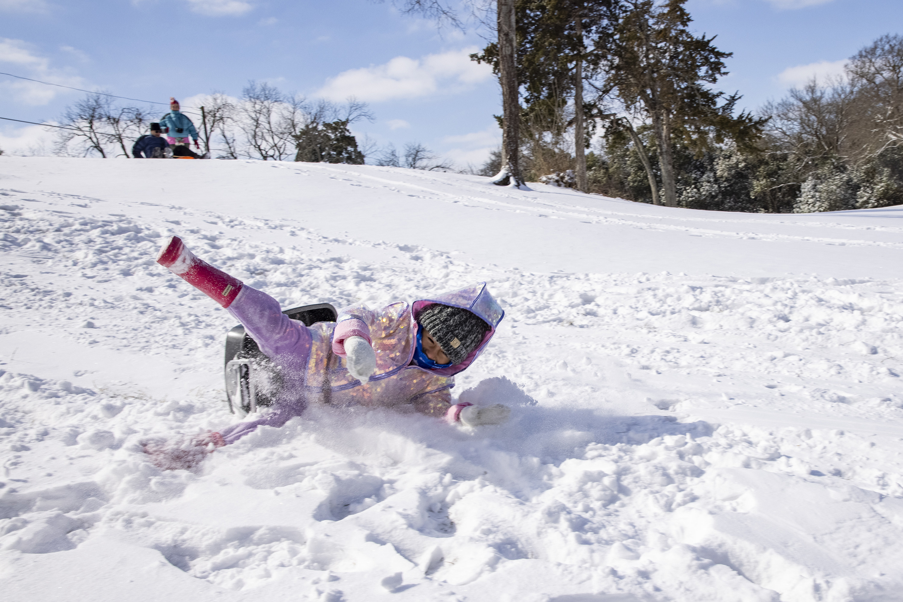 A young girl sledding down a hill