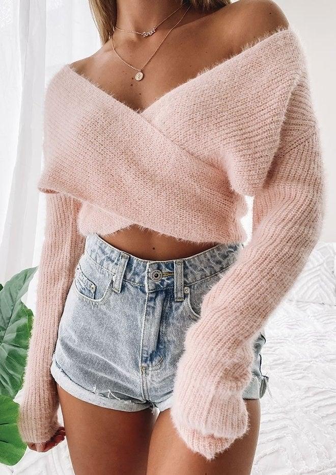 Model wearing pink fluffy criss-cross sweater