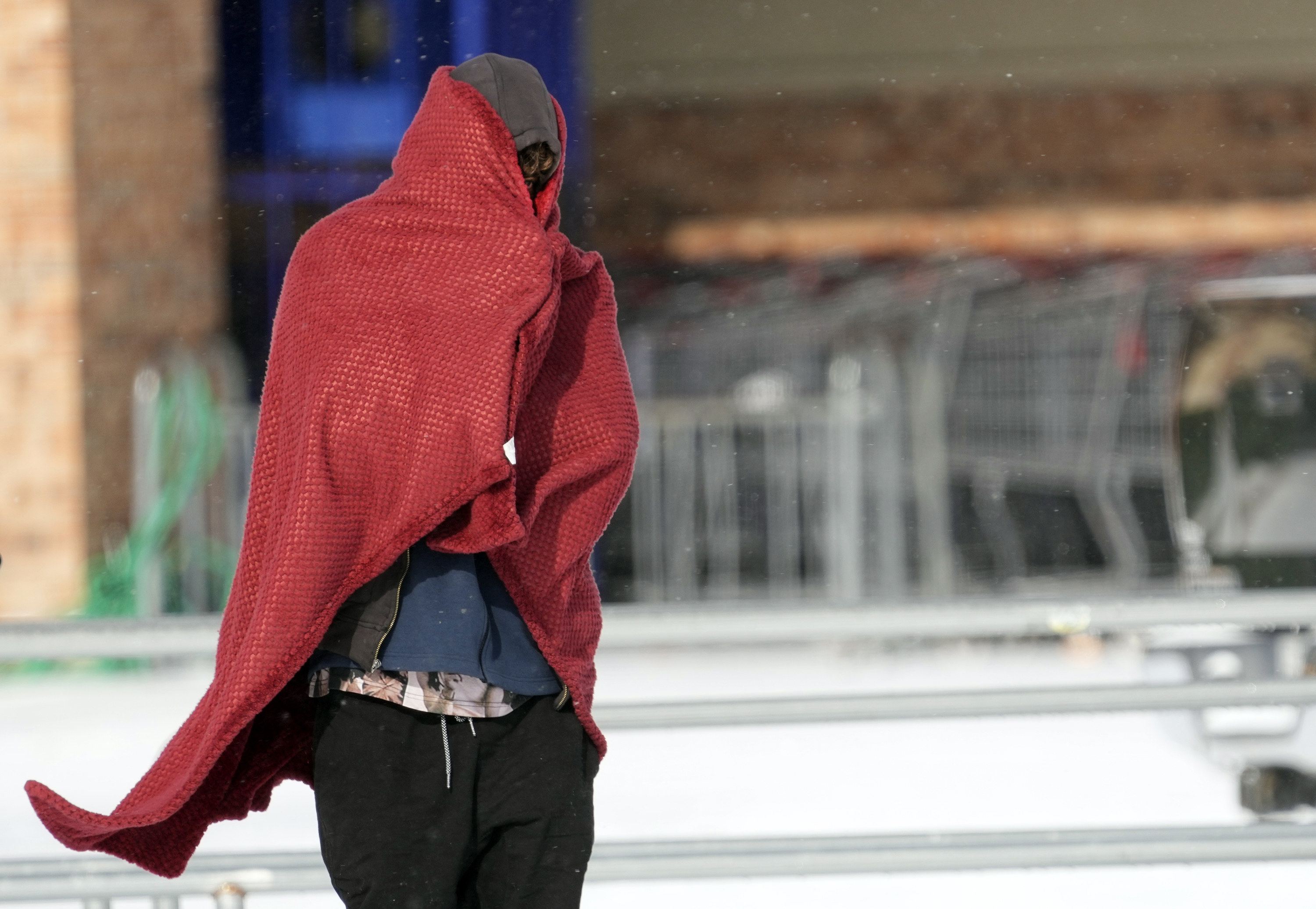 A man walks around with a sweatshirt and blanket to stay warm