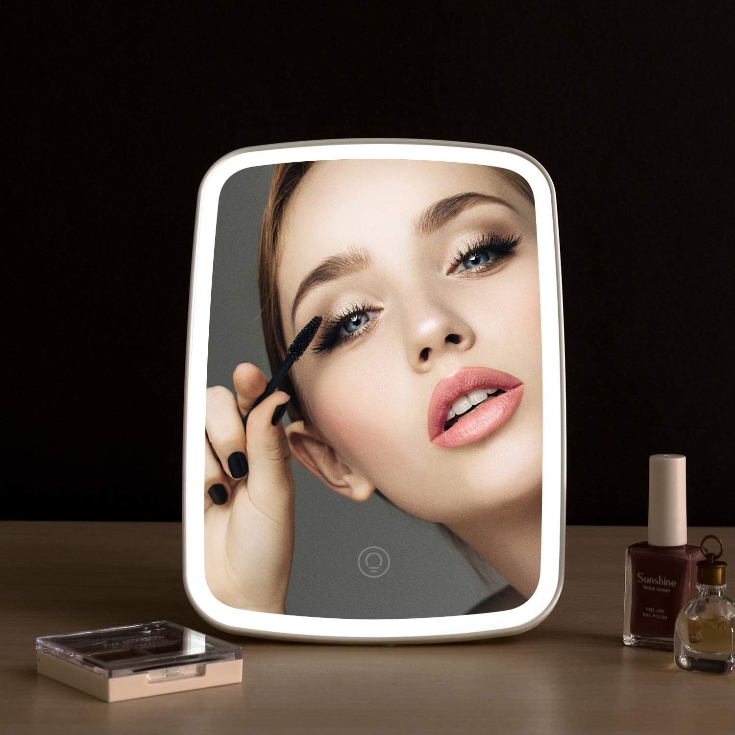 A person applying mascara in the lit-up vanity mirror