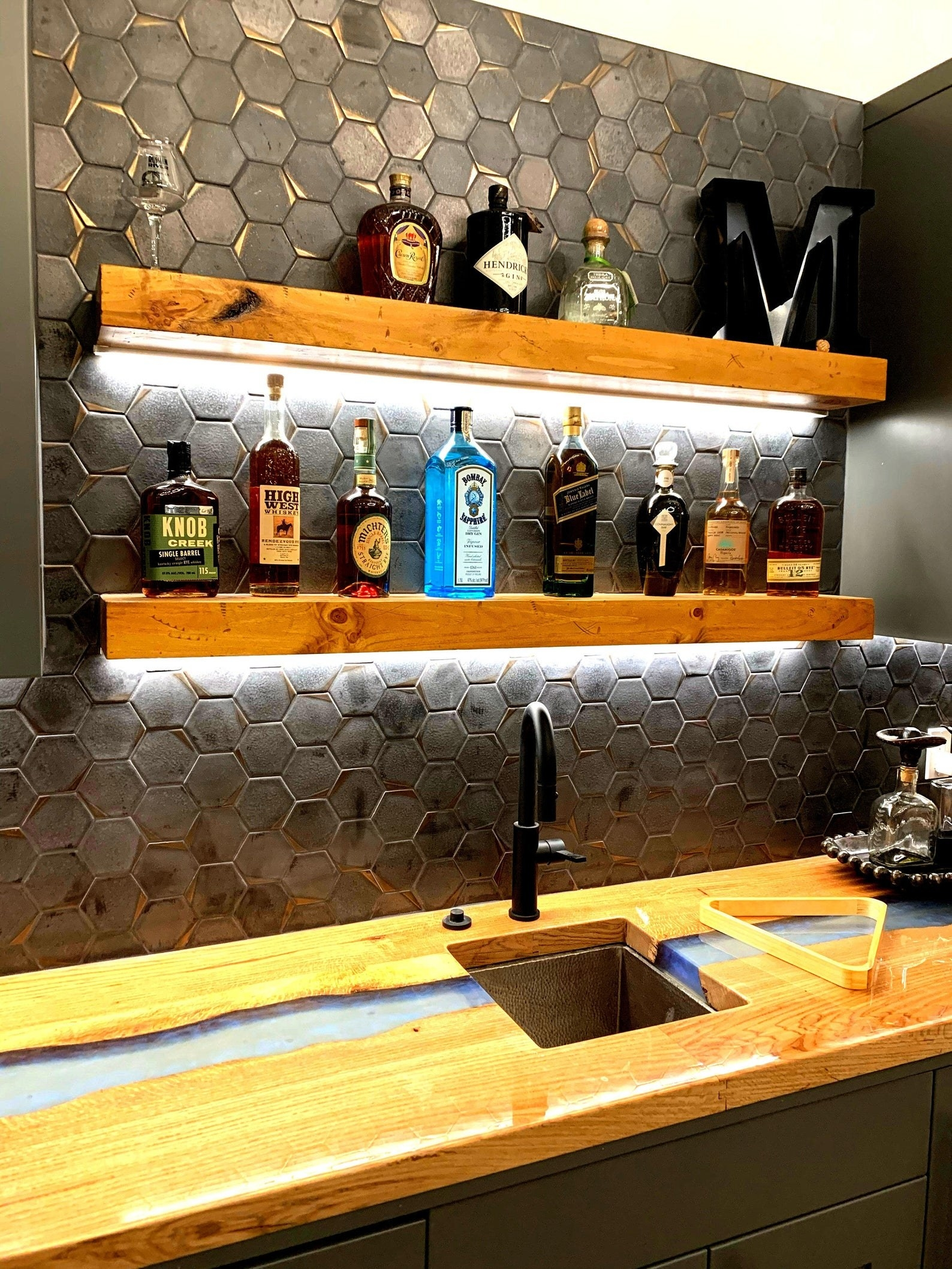 the floating shelves with alcohol bottles