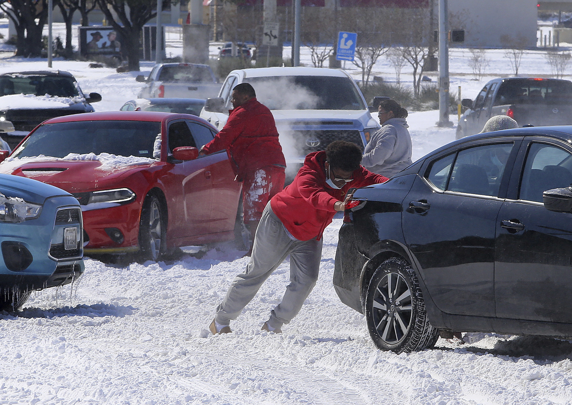 People at a crowded snowy intersection try to push their cars out of harm's way