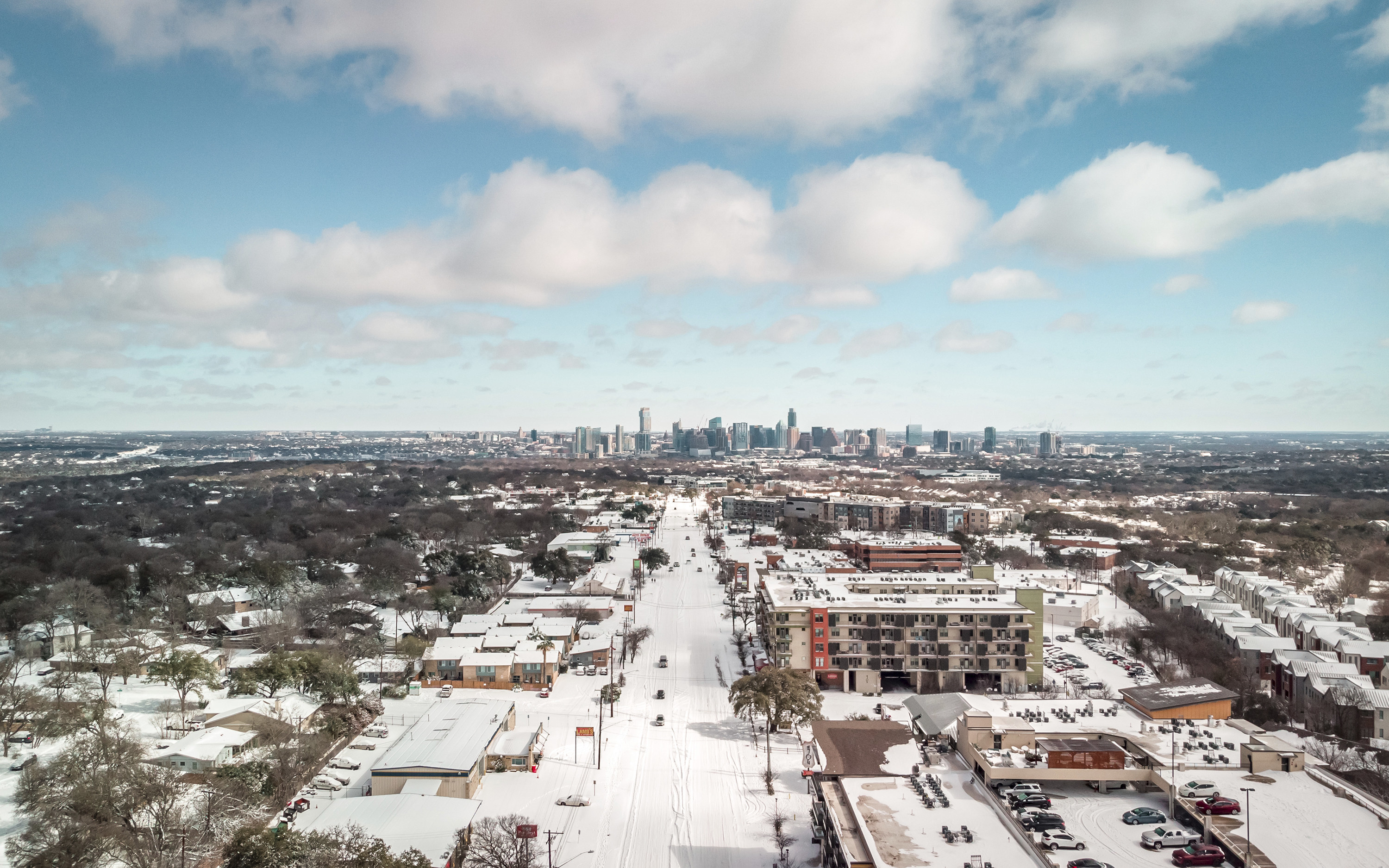 A snowy overhead scene in Austin showing snow-covered streets and a few cars
