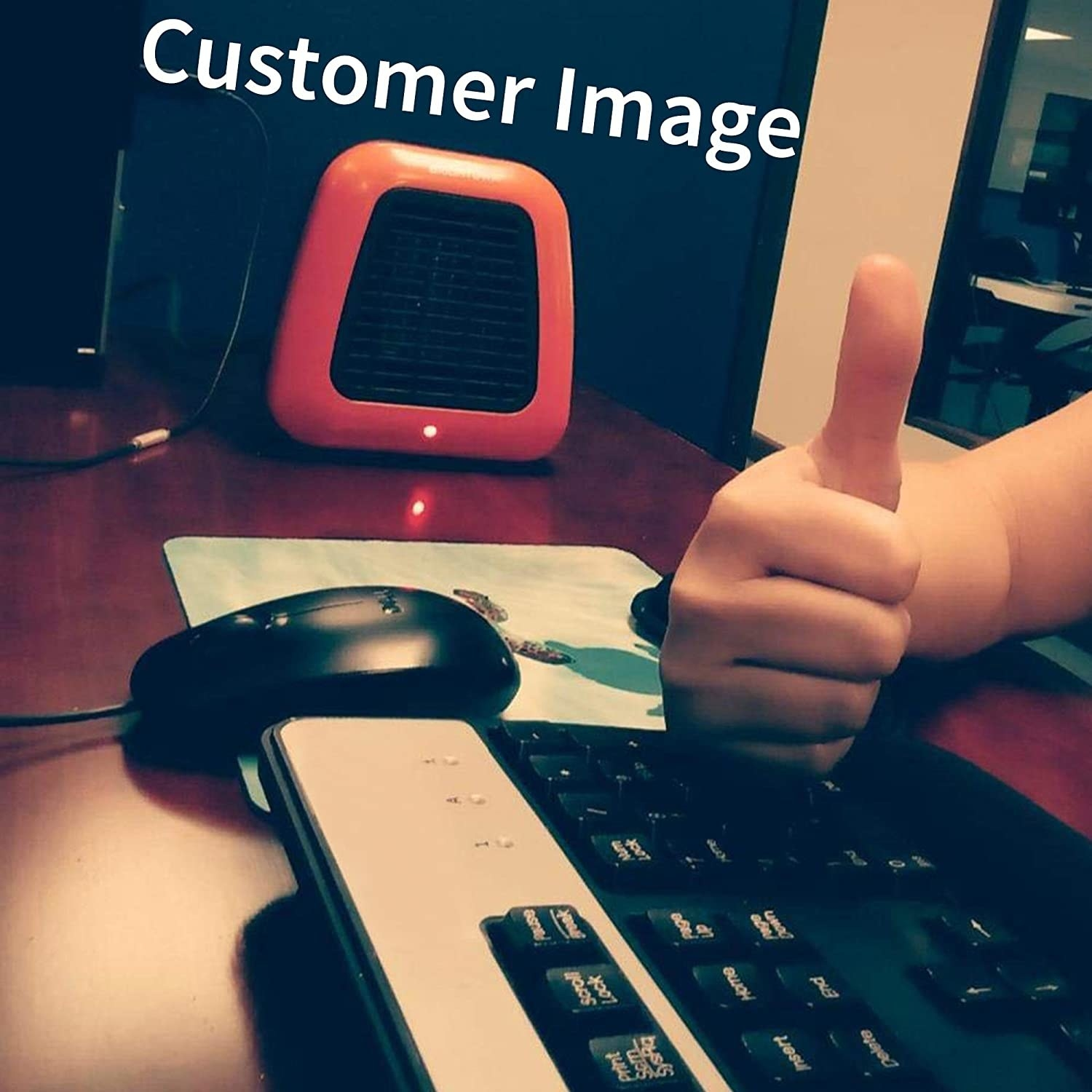 A reviewer photo of the space heater on the desk and the reviewer giving a thumbs up