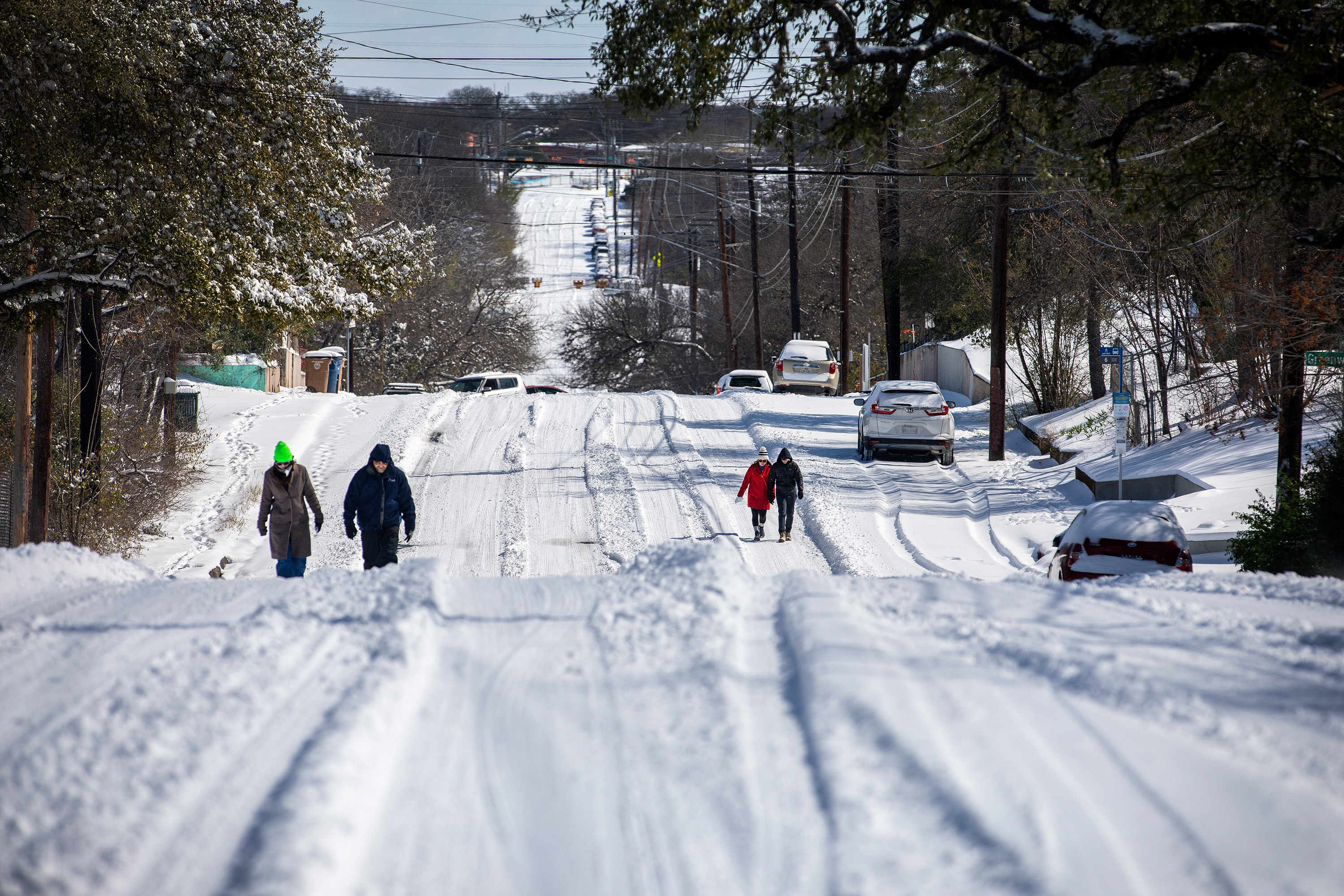Two pairs of people walking down extremely snowy roads in Texas