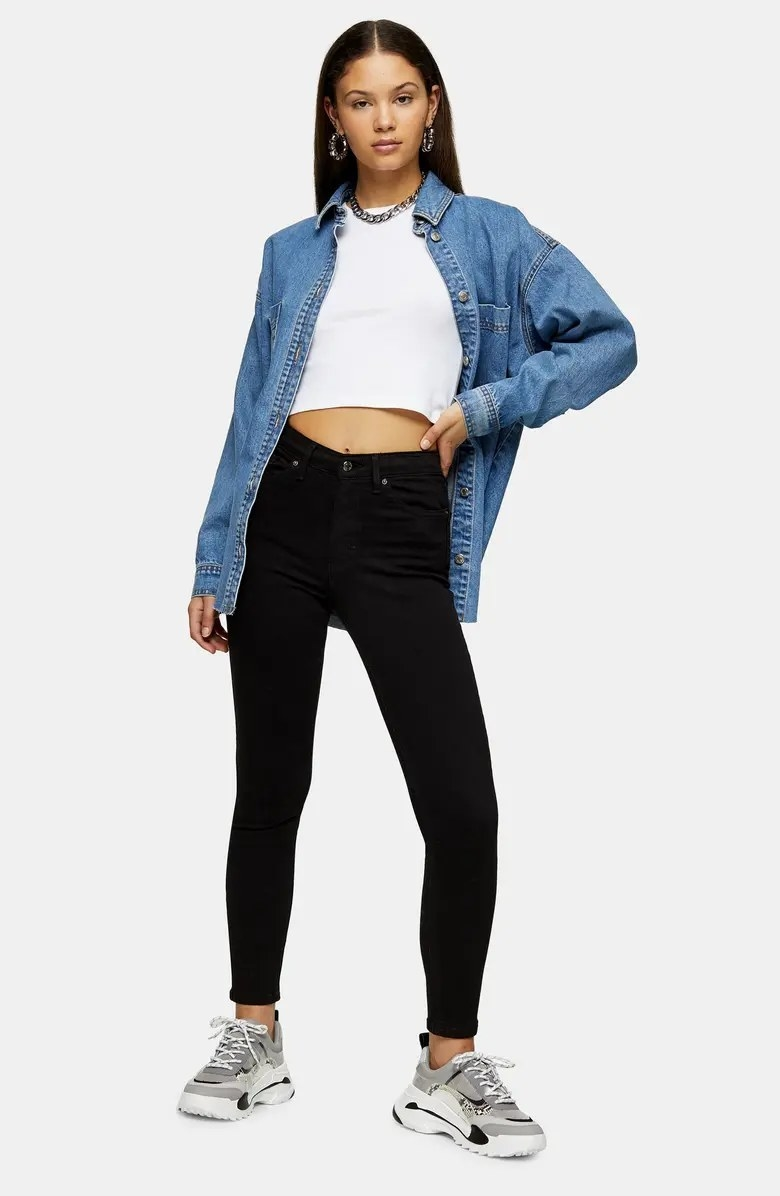 A model posing for the camera while wearing the black jeans