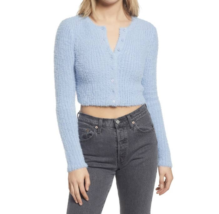 Model is wearing a light blue fuzzy crop cardigan and dark skinny jeans