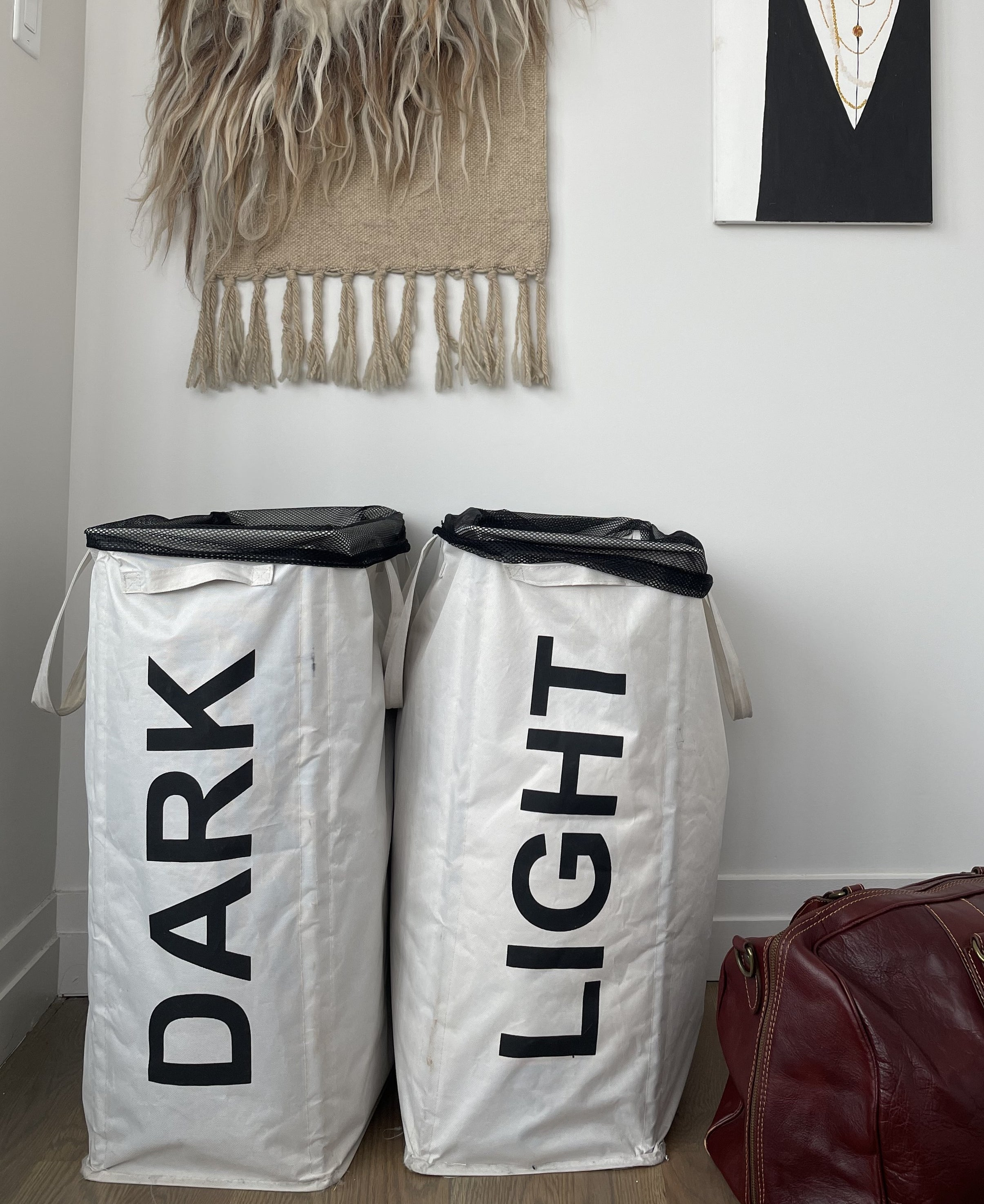 """buzzfeed writer's two cloth laundry hampers with handles and mesh bags inside, one says """"Dark"""" and the other """"Light"""""""