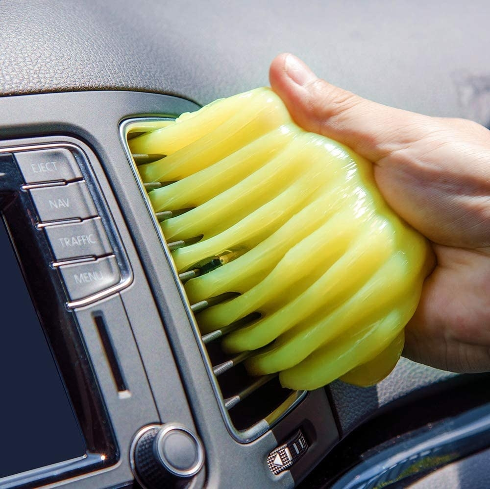 A person using the slime to clean their car vents