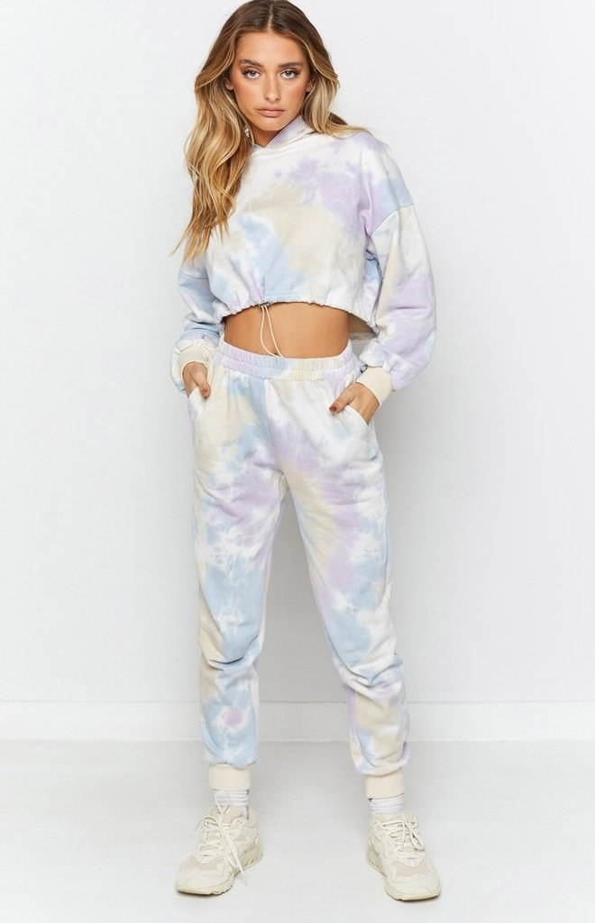 a model wearing a tie dye set with pastel blue, yellow, and purple