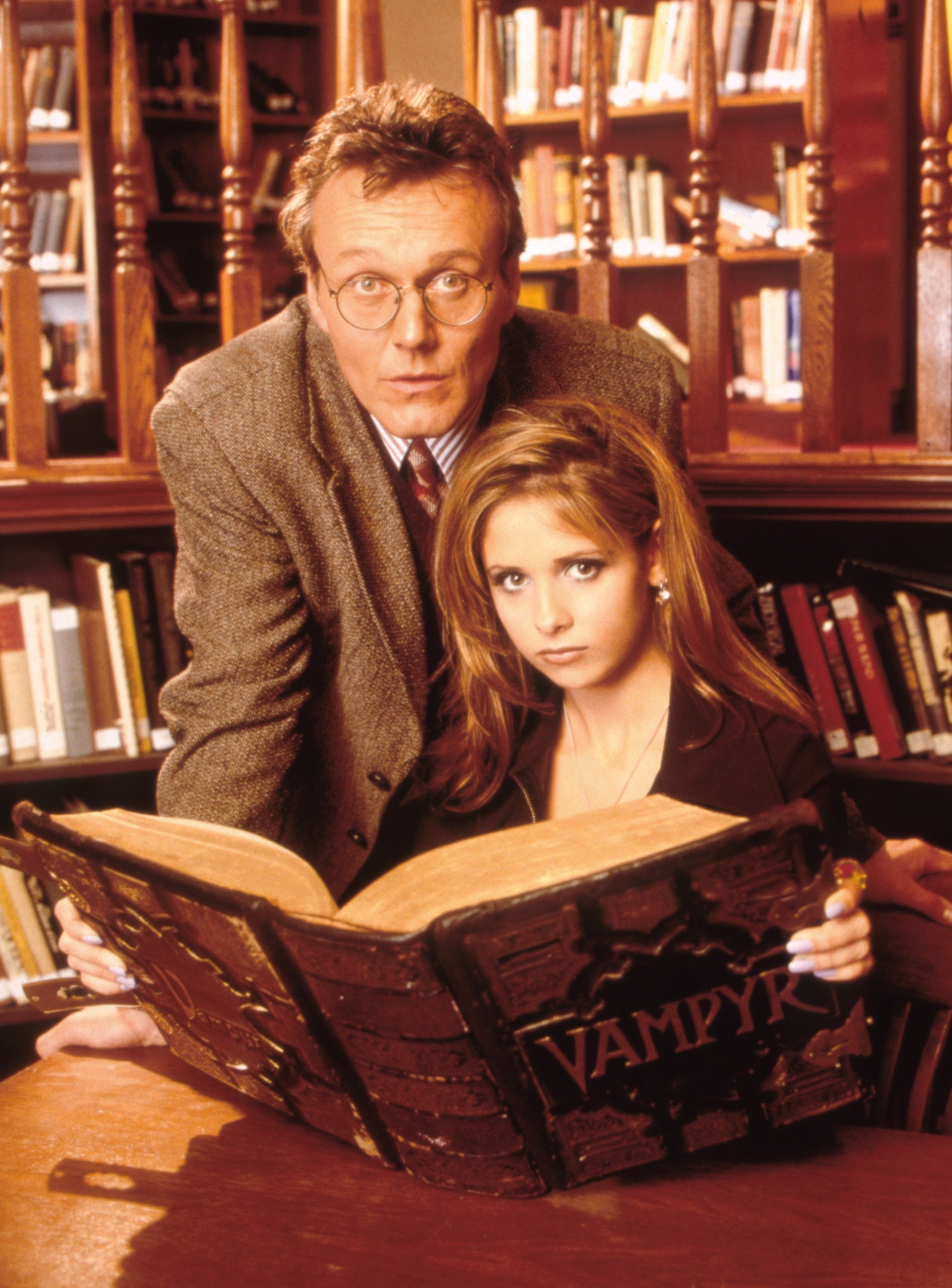 Giles standing next to Buffy as she holds open a book with the title 'Vampyr'