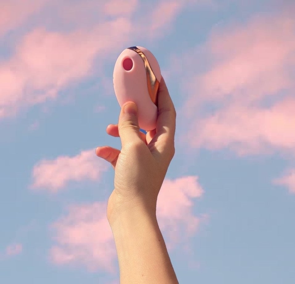 hand holding the light pink toy