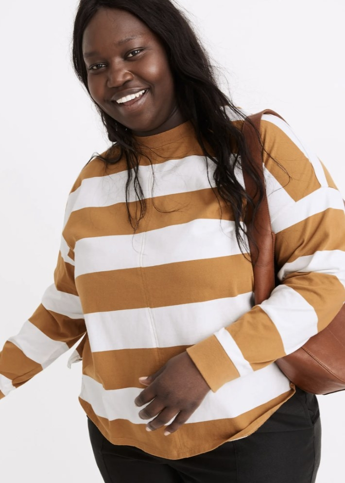 Model is wearing a tan and white stripes long sleeve shirt