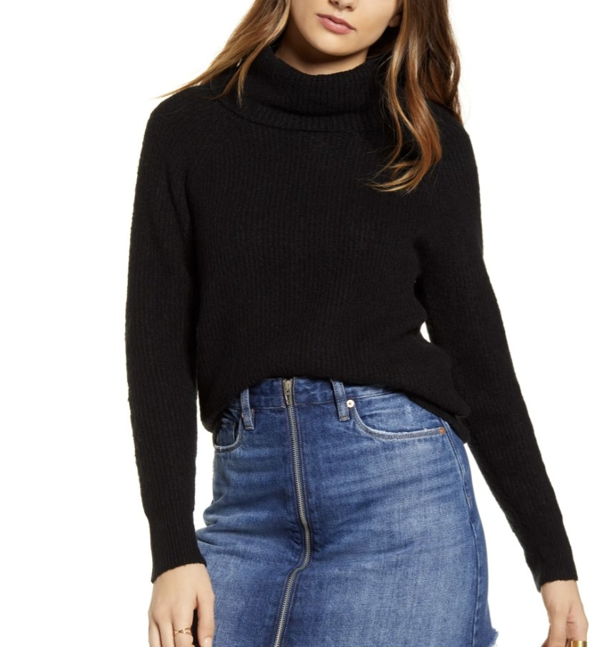 Model is wearing a black ribbed turtleneck sweater