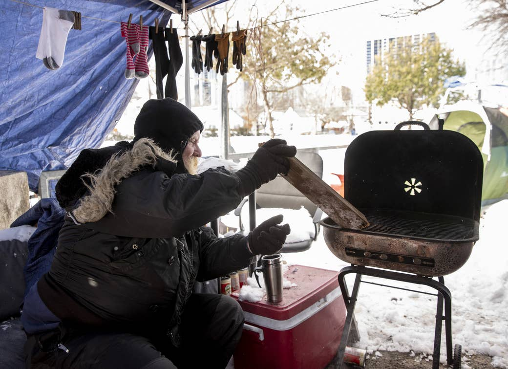 A homeless man uses a grill for heat