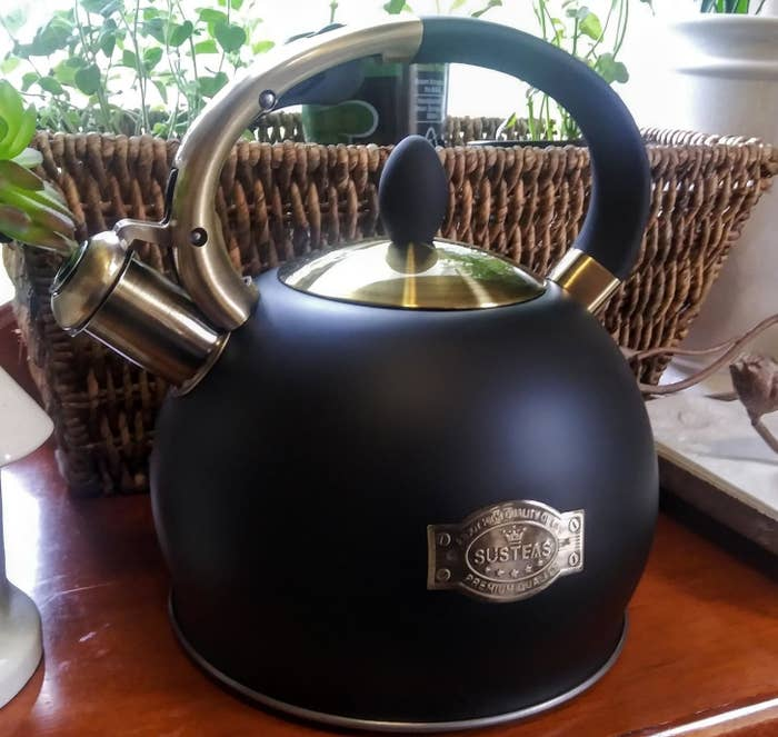 Black matte tea kettle with brass-colored spout, lid, and handle