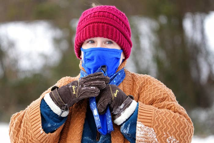 A white woman outdoors wearing a pink beanie, blue cloth mask, brown gloves, and an orange knit sweater