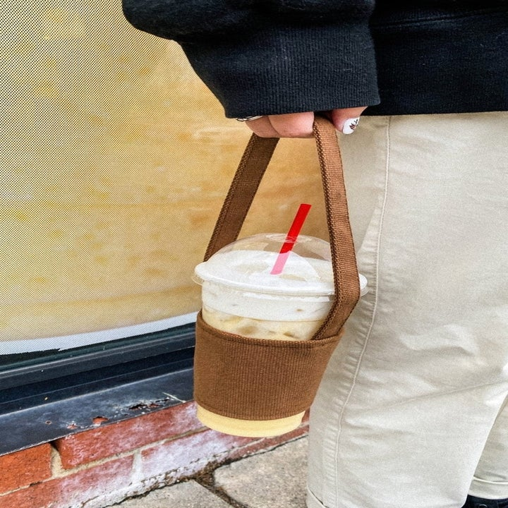 a model holding the cafe au lait holder with a coffee in it