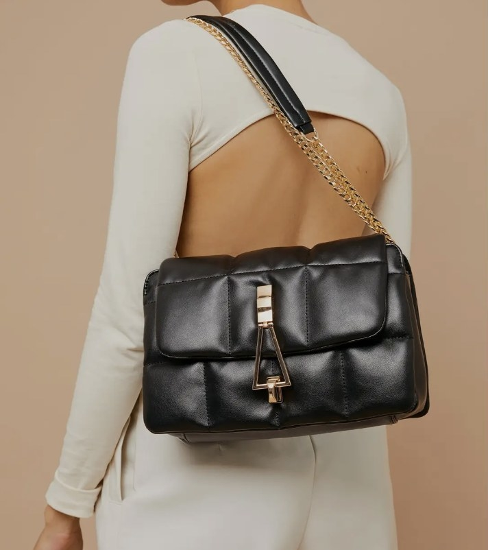 Model is holding a faux leather quilted shoulder bag