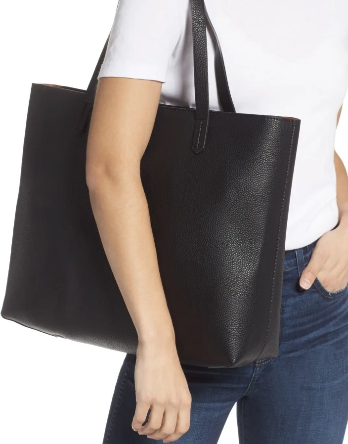 Model is holding a black faux leather tote bag