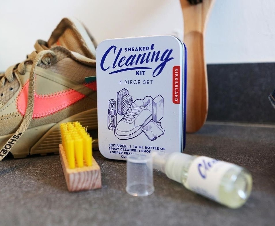A close up of the shoe cleaning kit next to a pair of dirty sneakers