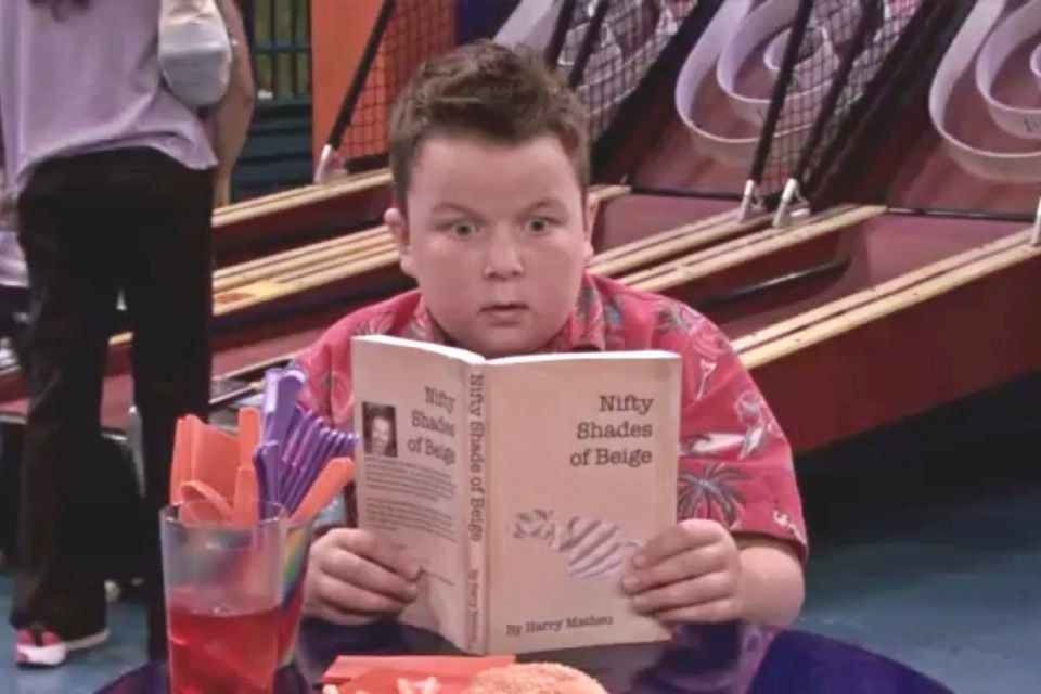 """Guppy sitting at an arcade with a terrified expression on his face as he reads a copy of """"Nifty Shades of Beige."""""""