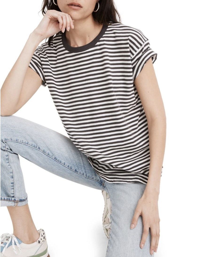Model is wearing a short-sleeved striped T-shirt and light denim jeans