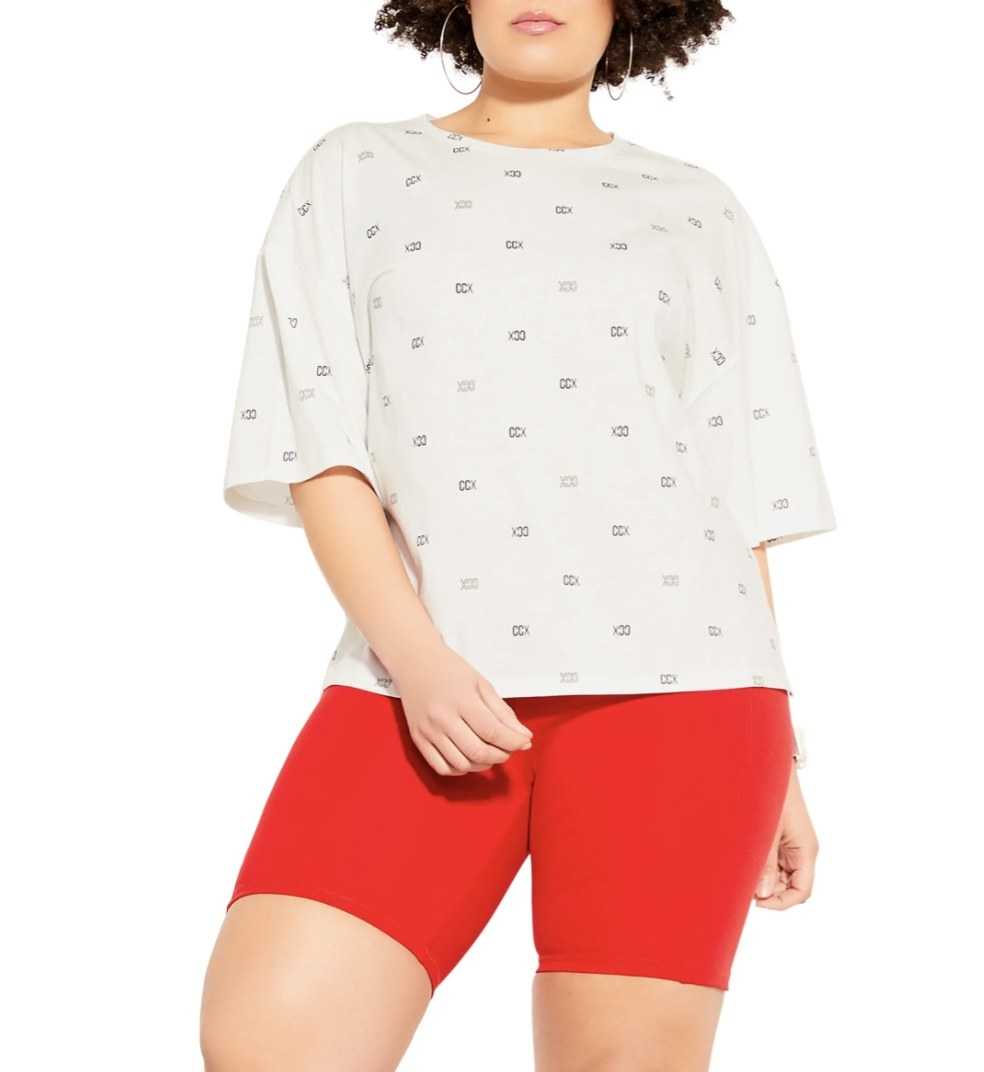 Model is wearing a white graphic tee and red bicycle shorts