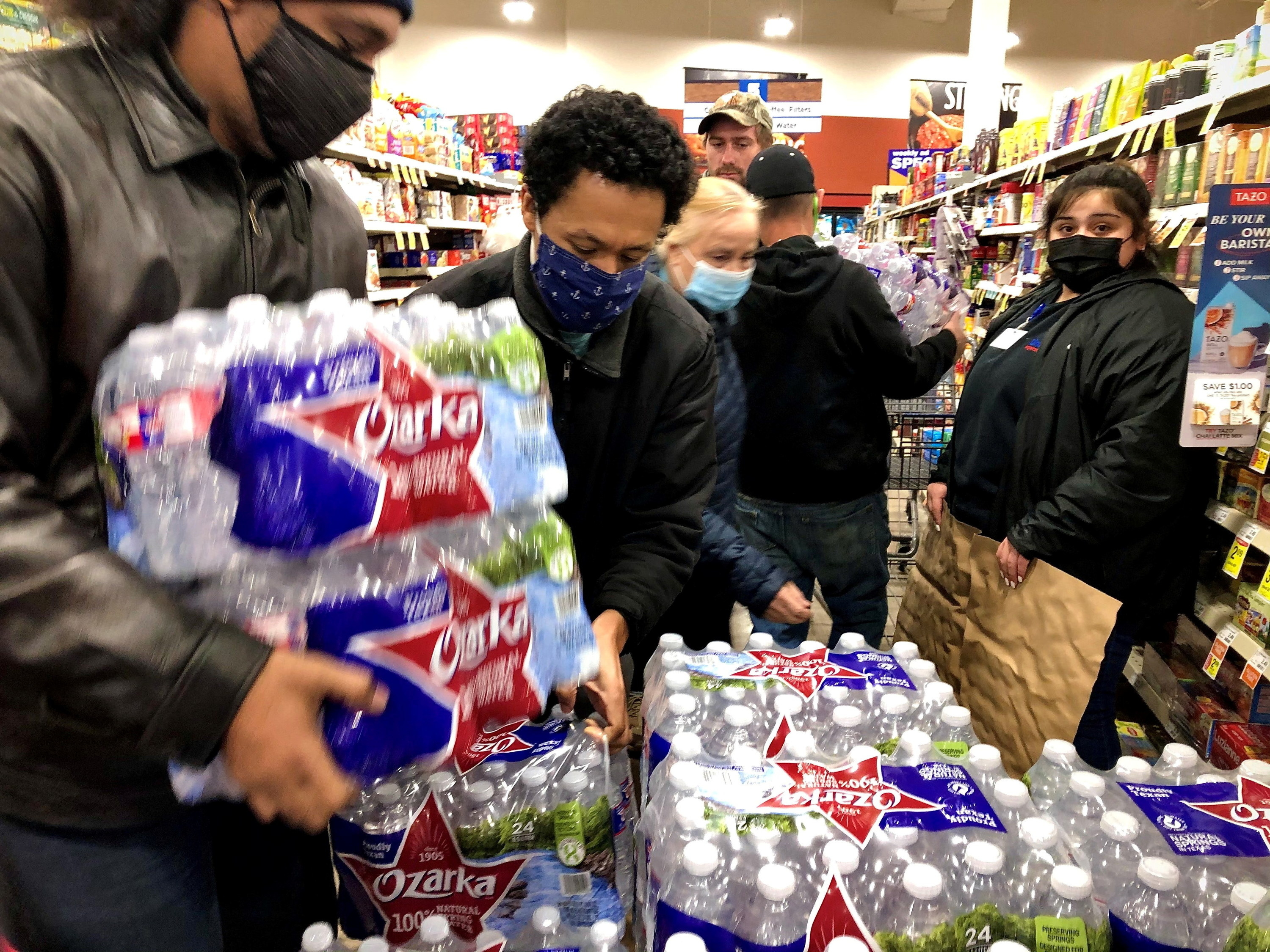 People grabbing at cases of water in a supermarket