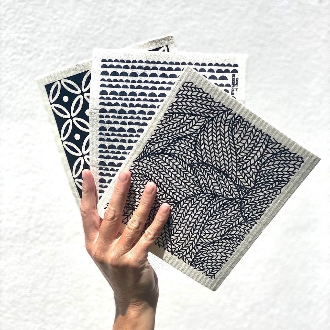 Someone holding up a trio of printed cellulose cloths