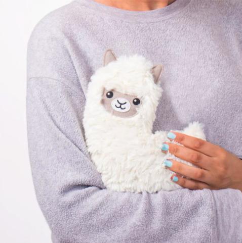 A person hugging a llama shaped heating pad