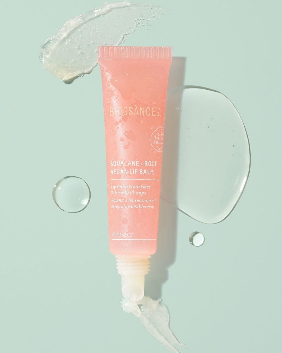 A tube of the lip balm on a simple background next to a smear of the product to show texture