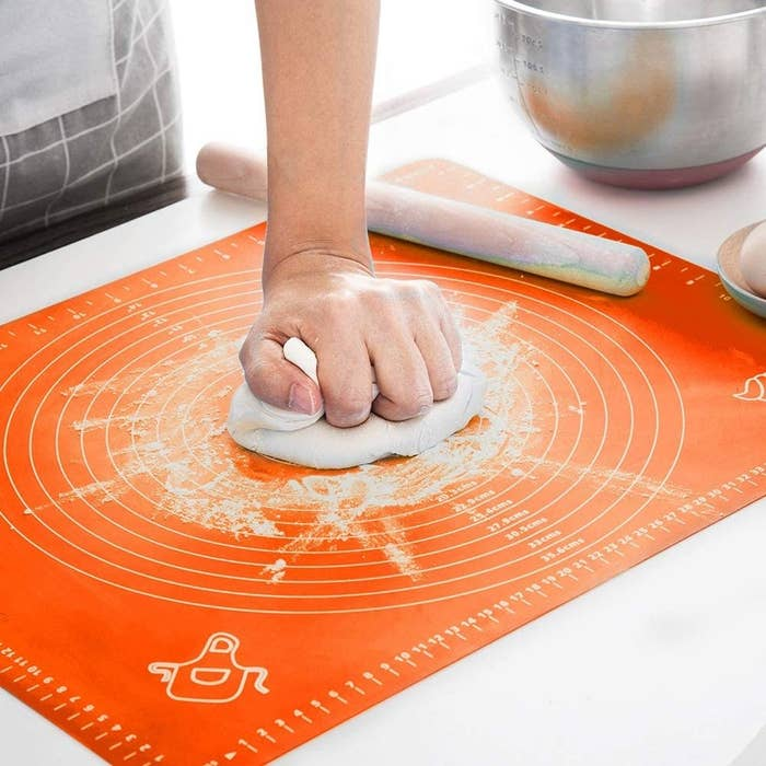 A person slamming dough down on the mat