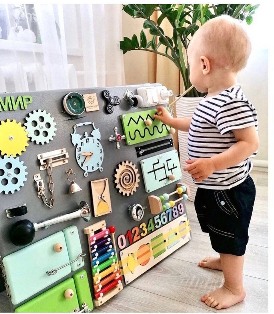 a toddler playing his a large busy board that featured various knobs, instruments, colors, numbers, wheels, and more