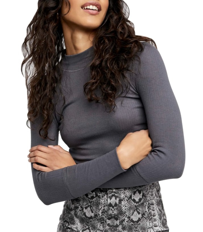 Model is wearing a charcoal grey mock neck long sleeve shirt with patterned pants
