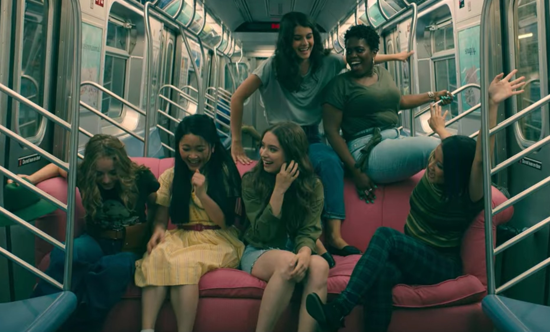 Lara Jean and friends sit on a couch inside of a subway train