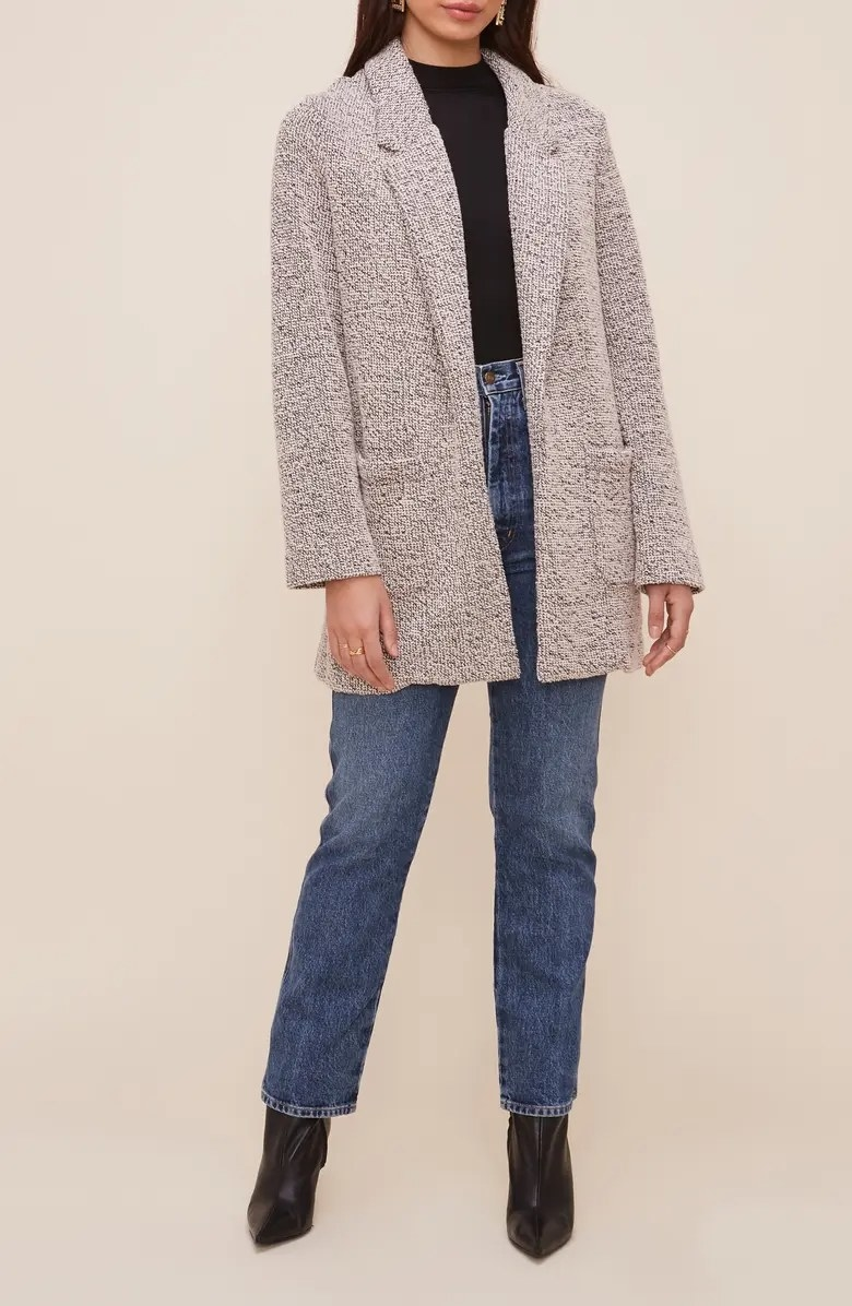 The blazer worn with a black top and blue jeans