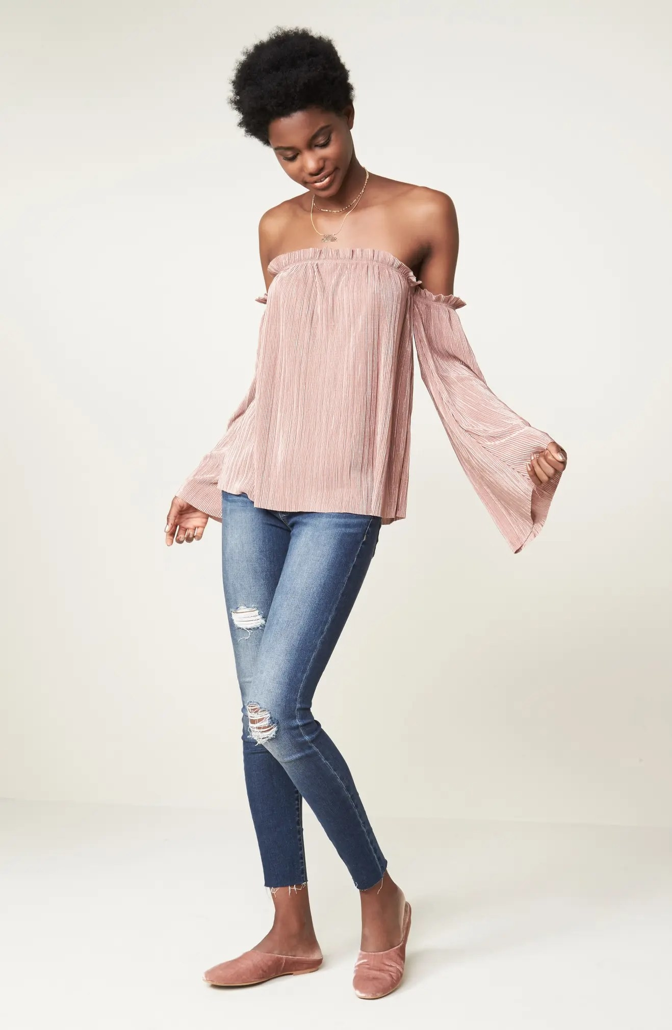 A model wearing the jeans with a pink blouse