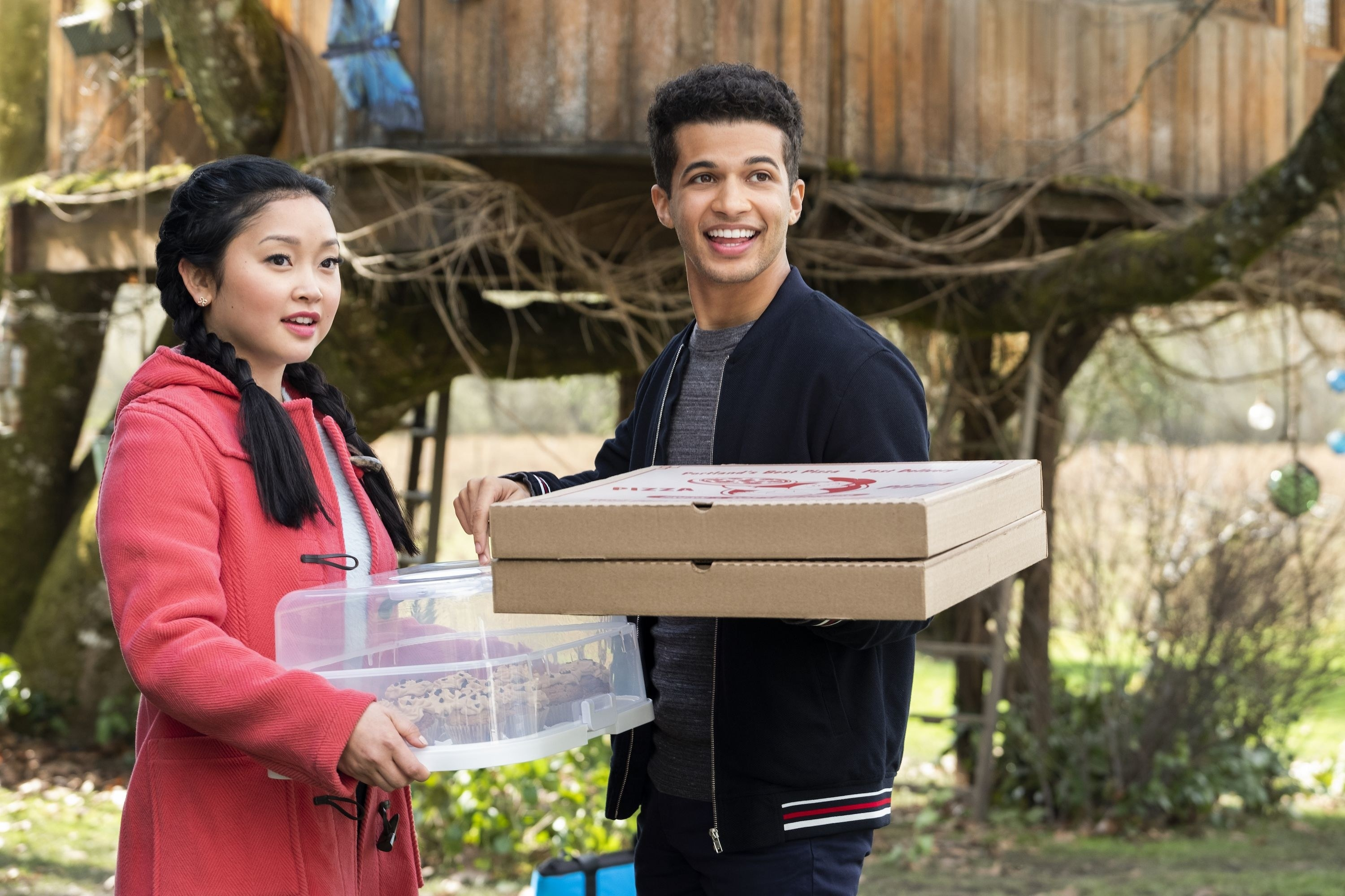John and Lara stand together holding pizza and baked goods