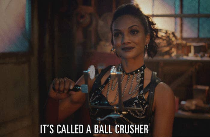 """A woman in leather and chains holds a device and says """"It's a ball crusher"""""""