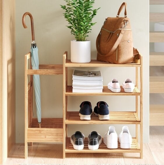 A bamboo shoe rack with four shelves and a built-in umbrella holder