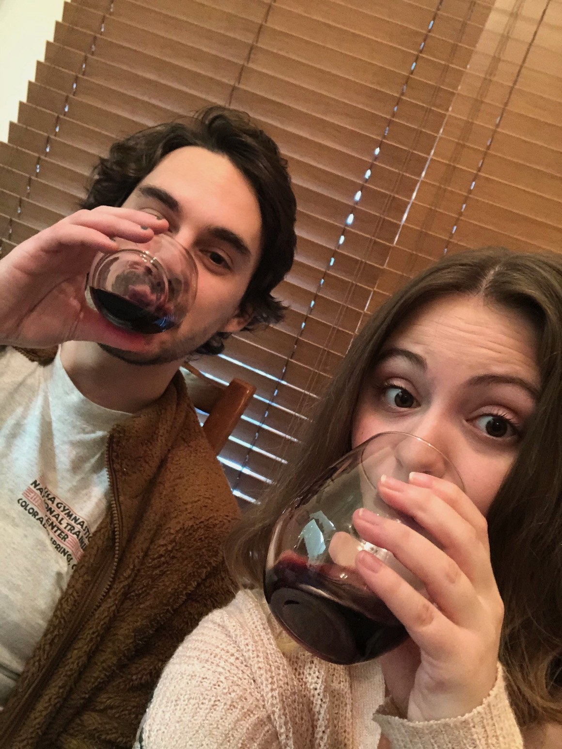 Young man and woman each drinking glasses of red wine