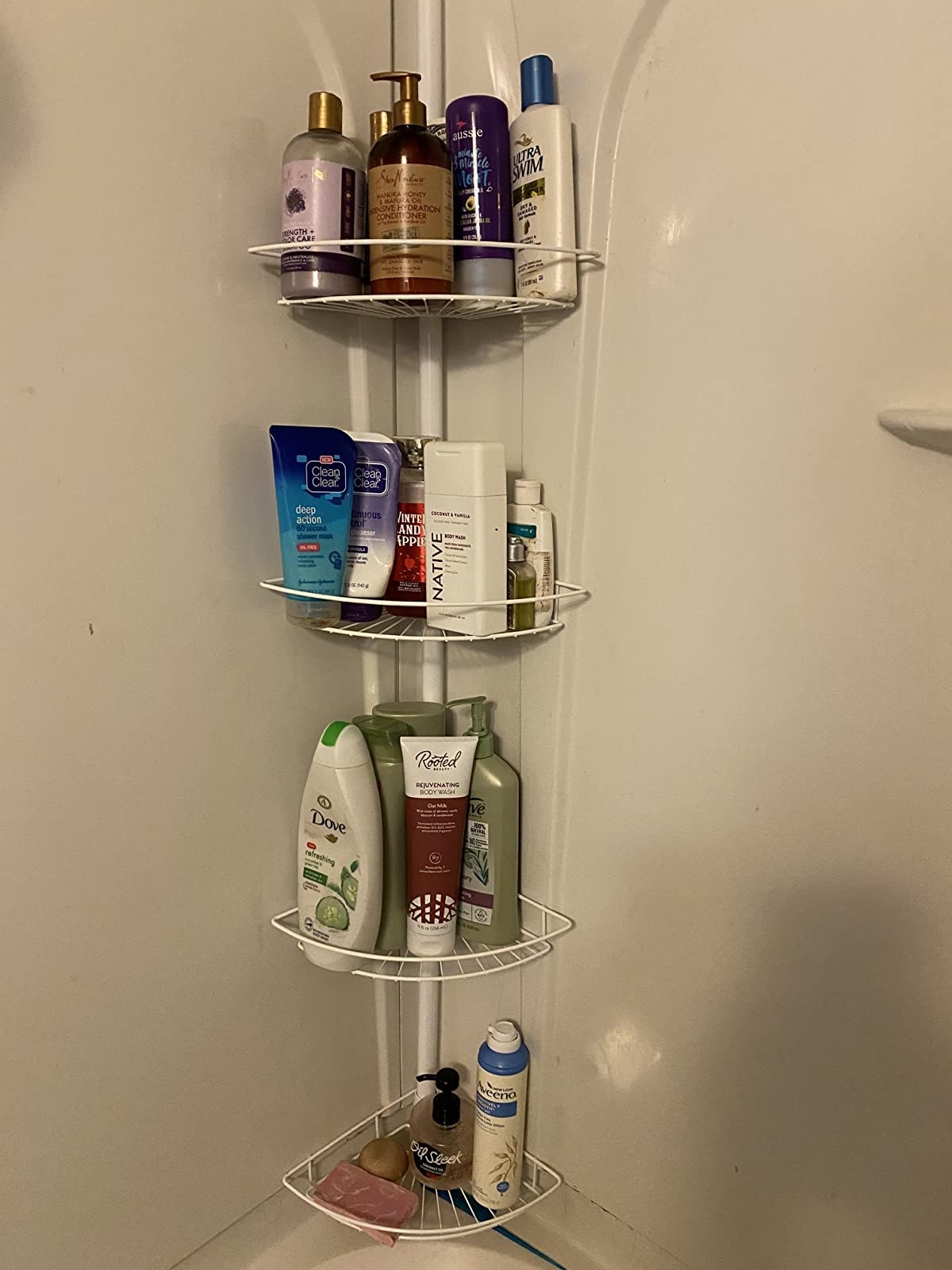 A reviewer photo of the four-tier shower caddy filled with shampoo bottles and other bath products
