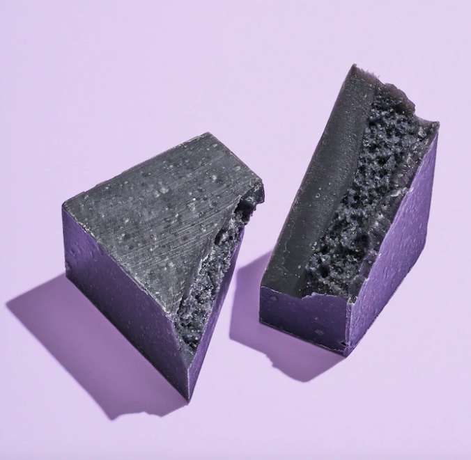 The charcoal soap bar cut diagonally and arranged artfully on a simple background