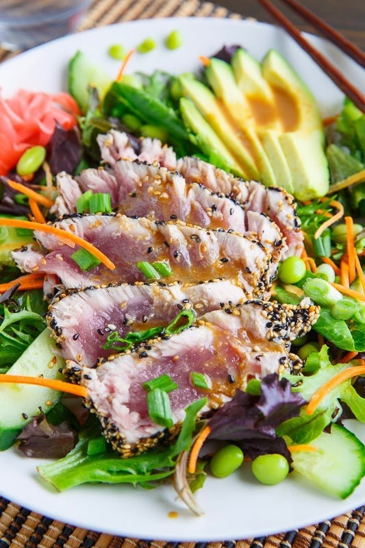 A salad with seared sesame crusted tuna, avocado, edamame, cucumbers, and carrots.
