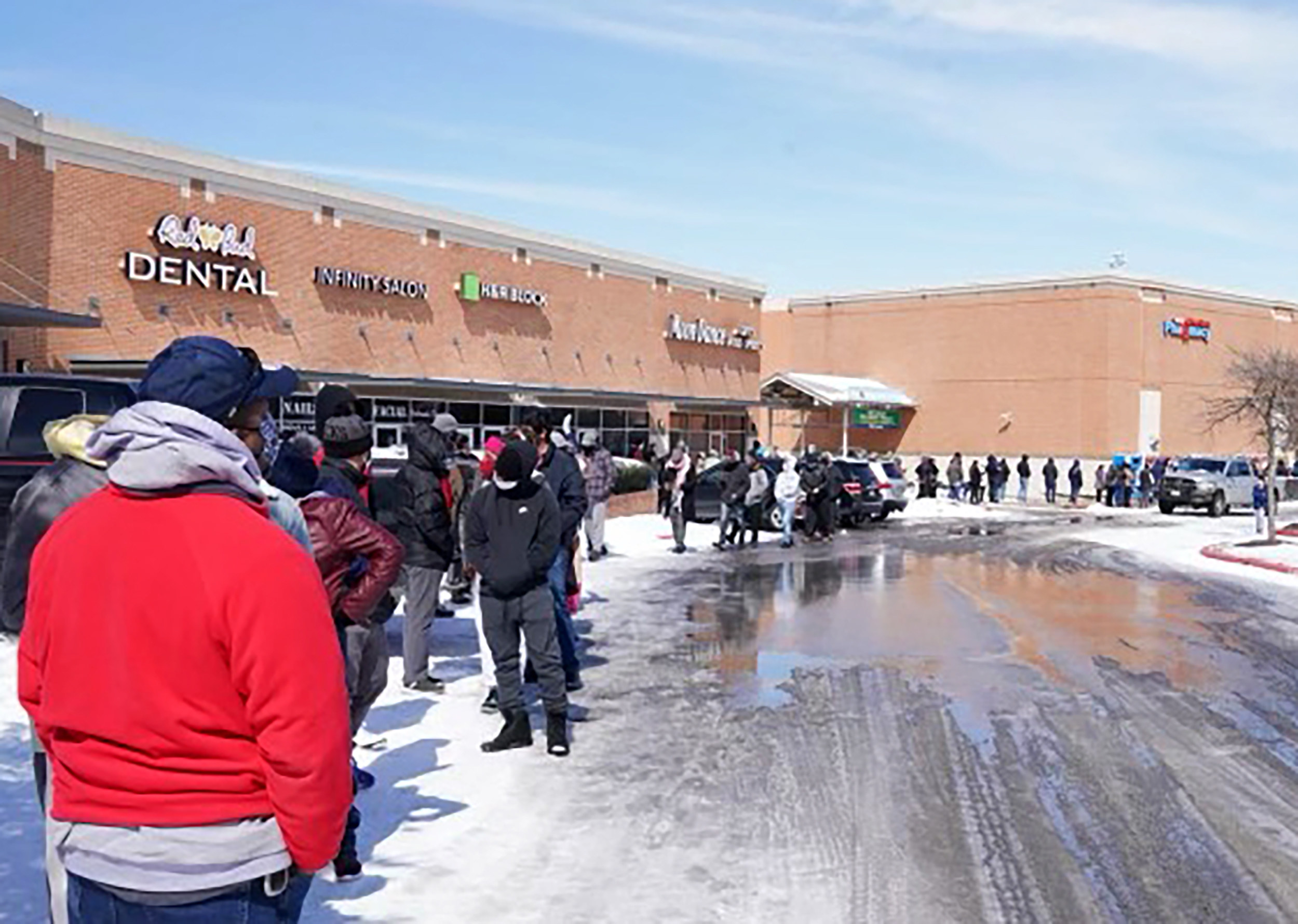 A long line of people waiting outside the supermarket