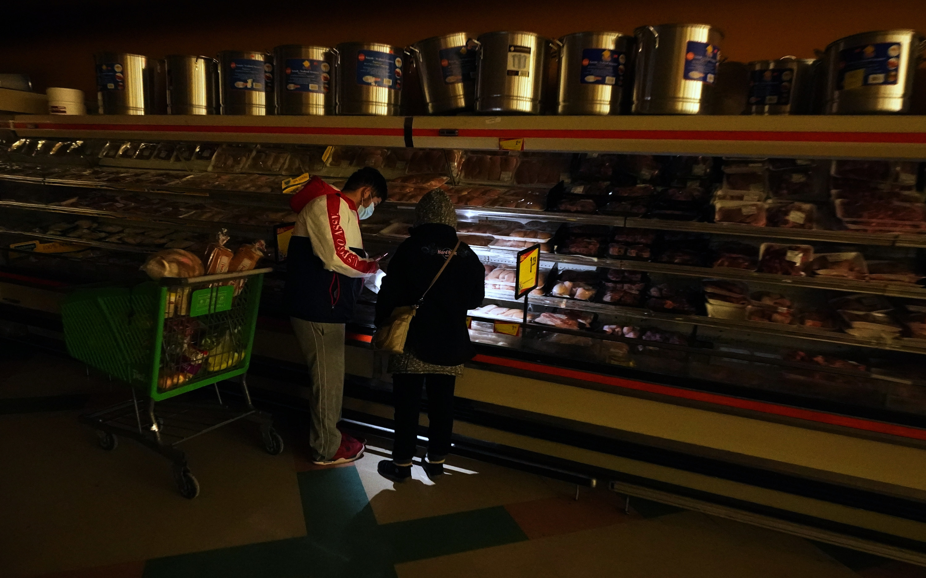 Two people buy meat in a supermarket with a flashlight as the power is out