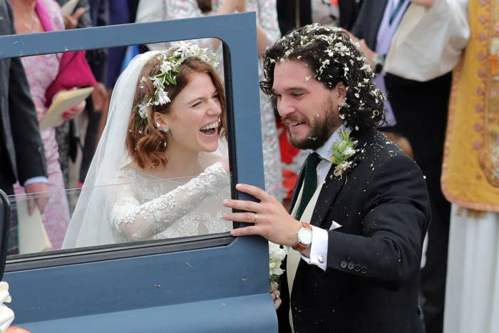 Kit and Rose smiling as they're about to get into a car on their wedding day