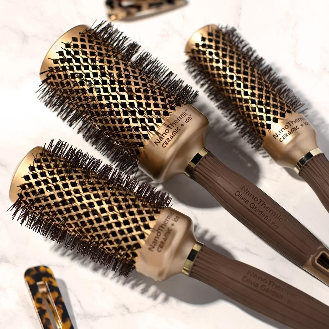three gold round hairbrushes in different sizes