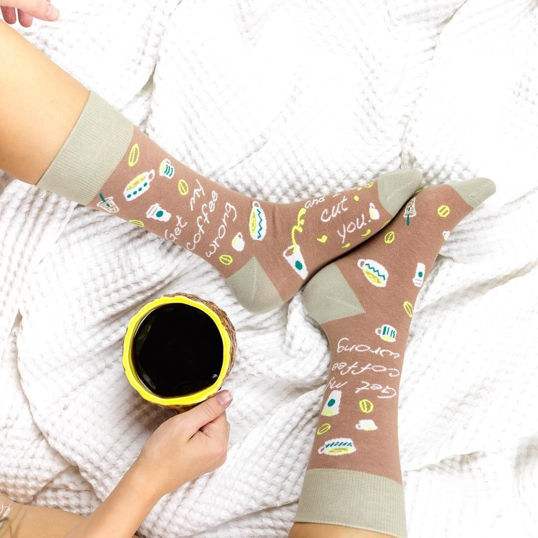 """a model wearing the socks which say """"get my coffee wrong and I cut you"""""""